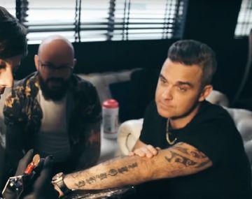 VIDEO: Robbie Williams y un integrante de One Direction se tatuaron el uno al otro